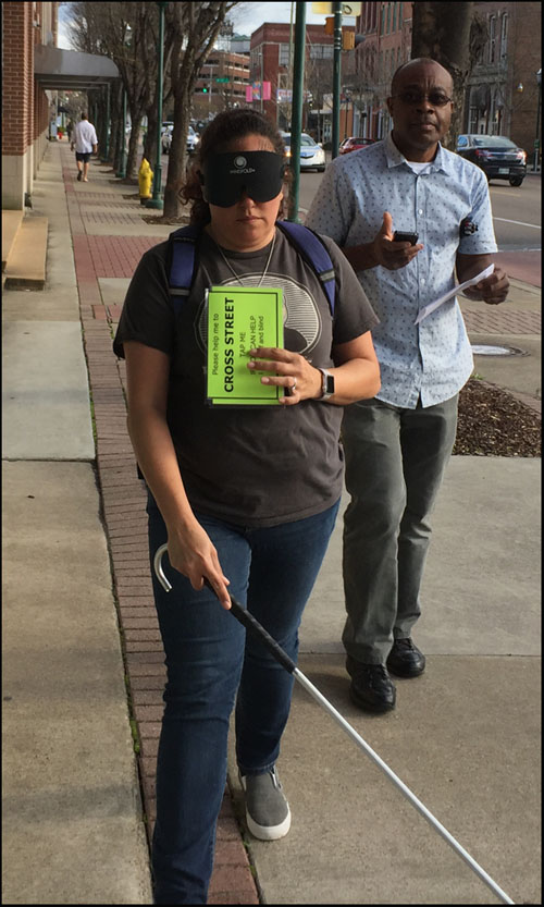 Photo shows a man and woman walking along a downtown sidewalk.  He is holding instructions for the Blindfold Walk, she is wearing a blindfold and using a cane, carrying a large card saying 'please help me to cross street, tap me if you can help.  I am deaf and blind.'