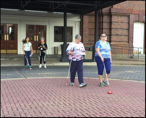 Photo shows 4 women walking from the front entrance of the hotel toward the street.  Two are walking with a blindfold and using a cane, two are carrying a cane and a paper with instructions.
