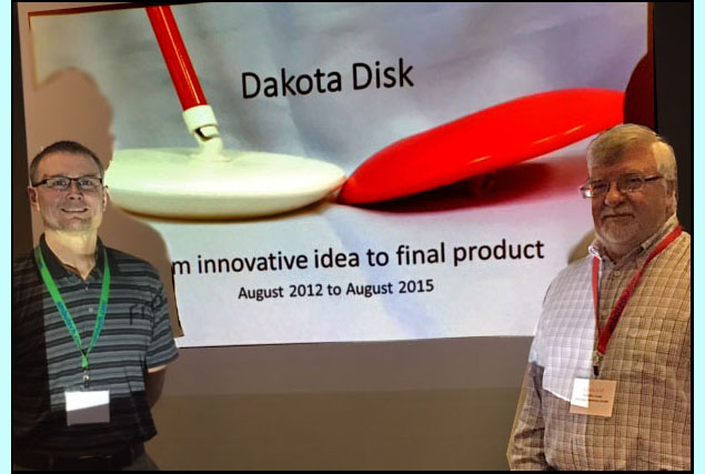 Paul and Gord are standing in front of their powerpoint which shows a red disk and a white disk each about 10 inches across and 1-2 inches high.  The white disk is attached to a cane and the slide says'Dakota Disk - From innovative idea to final market, August 2012 to August 2015'.