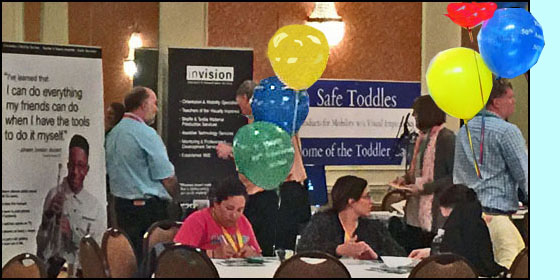 Photo shows exhibits for Invision and for Safe Toddles with people talking with the vendors.  In front of them are large round tables with balloons, and people sitting and chatting.