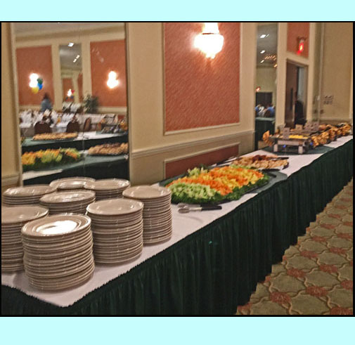 photos shows a long table with piles of plates colorful vegetables and 4 or 5 large steam tables.