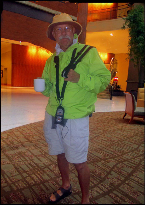 Craig is standing in the hotel lobby wearing an iridescent yellow-green windbreaker, white shorts, and a safari-type hat with a Trekker Breeze device hanging around his neck.  He is holding a coffee mug.