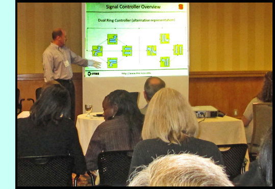 Chris Cunningham is standing on front of a room full of participants and points to diagrams on a powerpoint titled 'Signal Controler Overview.'