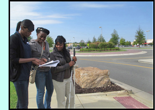 3 participants stand at a crosswalk and check their notes -- behind them we see a roundabout.